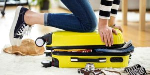 Woman kneels on luggage to zip it closed