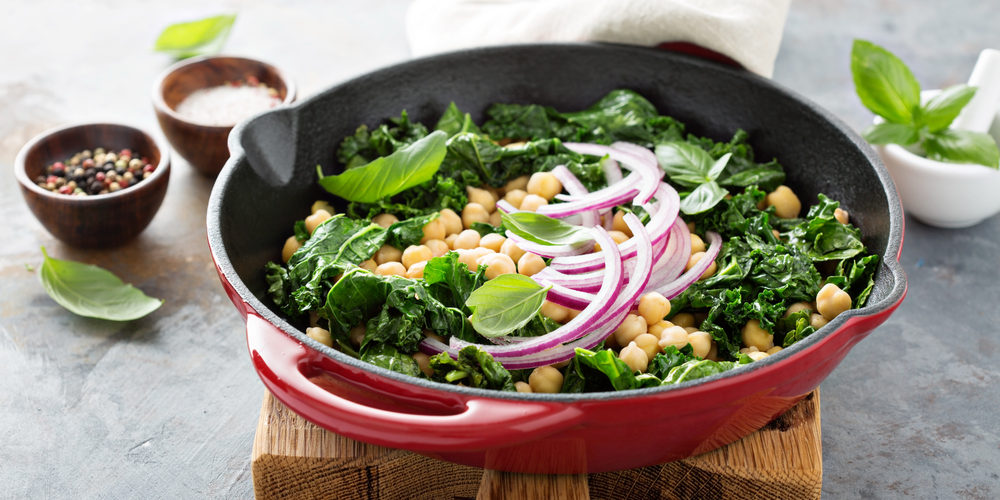 Sauteed kale with chickpeas and red onion - vegan dish in a cast iron skillet