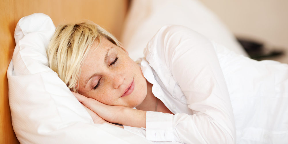 Relaxed young businesswoman sleeping on bed at home, eyes closed