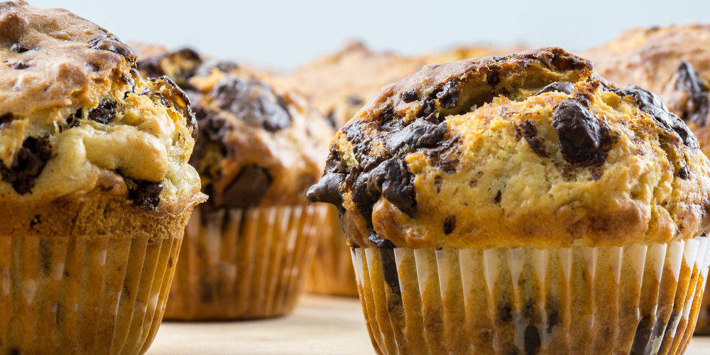 Delicious homemade chocolate chip muffins on wooden surface.