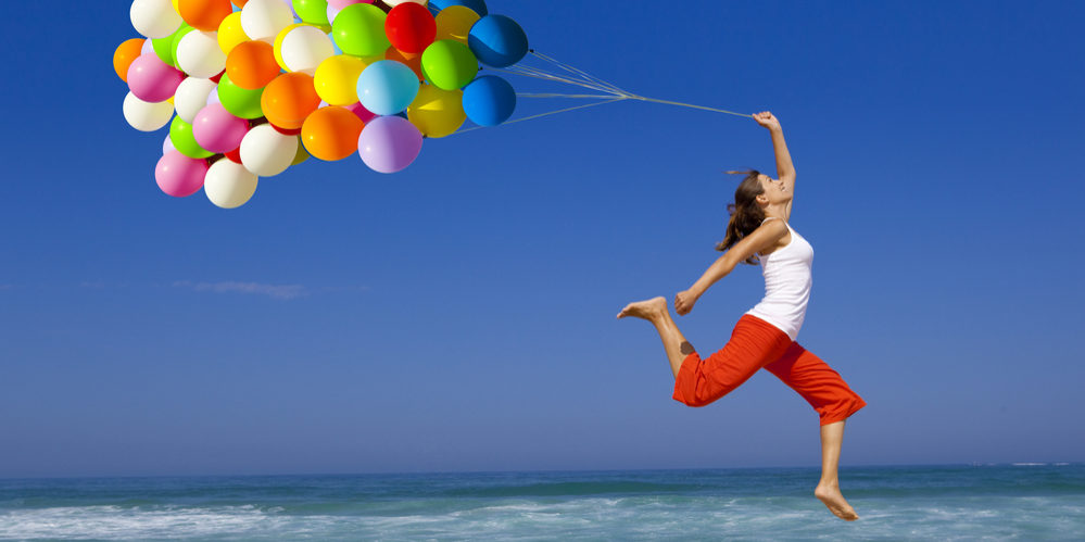 Beautiful and athletic Girl jumping with a balloon on the beach