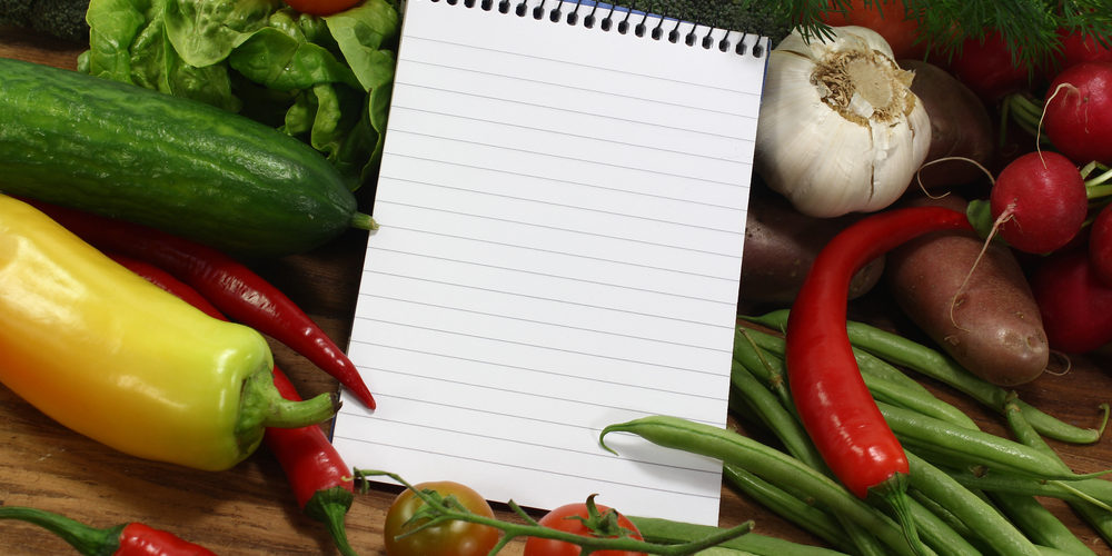 little ruled shopping list with vegetables on a wooden background